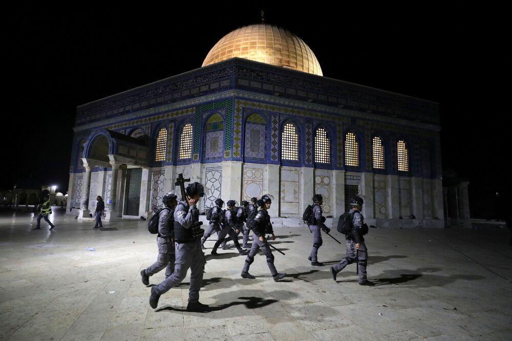 Polícia israelense caminha perto da Cúpula do Rochedo, durante confrontos na área da Mesquita Al-Aqsa, conhecida pelos muçulmanos como Santuário Nobre e pelos judeus como Monte do Templo, em meio a tensões motivadas pelo possível despejo de famílias palestinas de casas em terras reclamadas pelos colonos judeus no bairro Sheikh Jarrah, na Cidade Velha de Jerusalém, 7 de maio de 2021