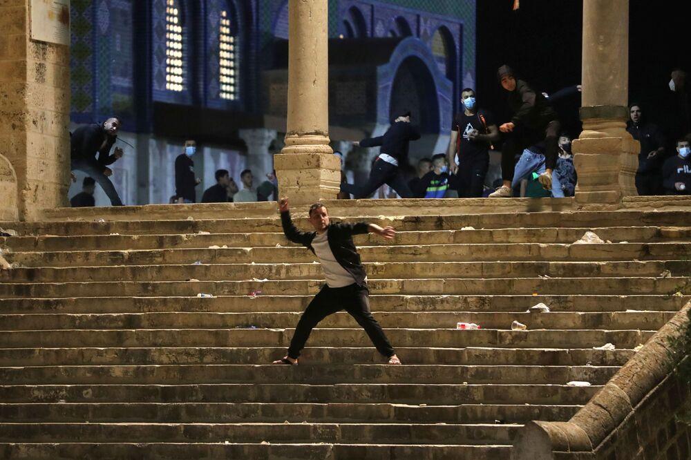 Palestino atira pedras na polícia israelense durante confrontos na área da Mesquita Al-Aqsa, conhecida pelos muçulmanos como Santuário Nobre e pelos judeus como Monte do Templo, em meio a tensões sobre o possível despejo de famílias palestinas de casas em terras reclamadas pelos colonos judeus no bairro Sheikh Jarrah, na Cidade Velha de Jerusalém, 7 de maio de 2021