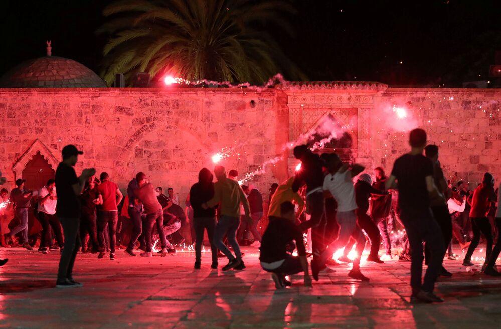 Palestinos reagem à polícia israelense disparando granadas atordoantes durante confrontos junto à Mesquita Al-Aqsa, conhecida pelos muçulmanos como Santuário Nobre e pelos judeus como Monte do Templo, em meio a tensões motivadas pelo possível despejo de famílias palestinas de casas em terras reclamadas pelos colonos judeus no bairro Sheikh Jarrah, na Cidade Velha de Jerusalém, 7 de maio de 2021
