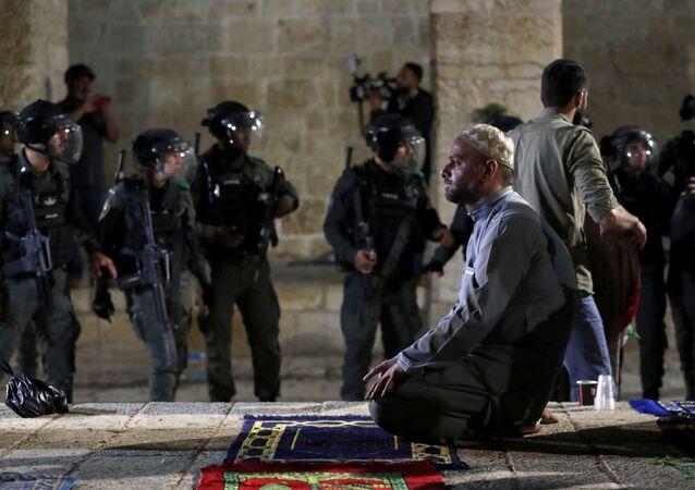 Um palestino ora enquanto a polícia israelense se reúne durante confrontos no complexo que abriga a mesquita de Al-Aqsa, 7 de maio de 2021.