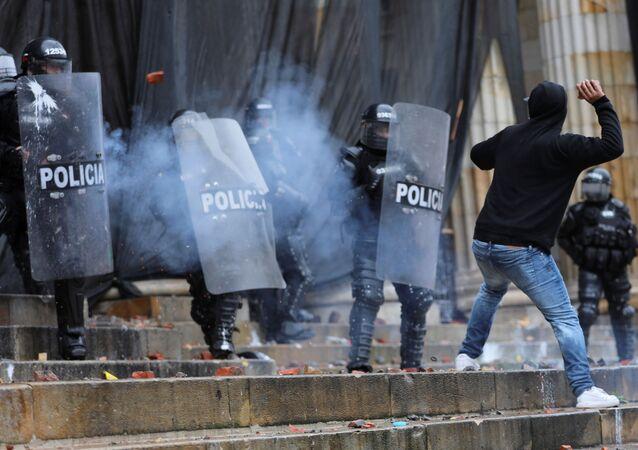Manifestante entre em confronto com policiais durante protestos em Bogotá, na Colômbia