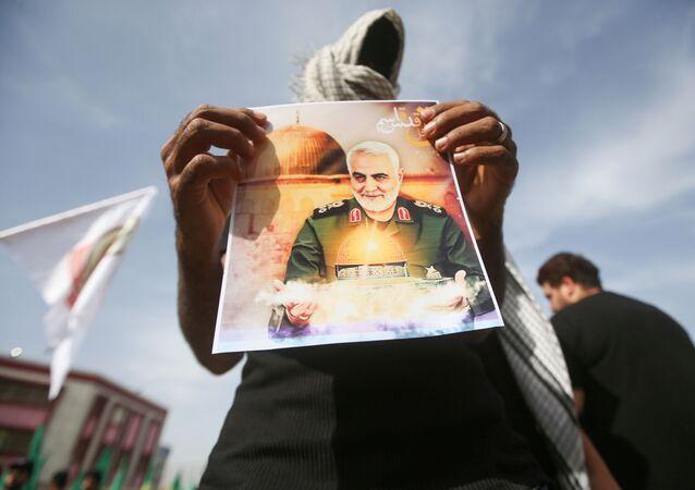Membro das Unidades de Mobilização Popular do Iraque (PMU, na sigla em inglês) mostra foto de Qassem Soleimani, general iraniano assassinado em 3 de janeiro de 2020, em Basra, Iraque, 7 de maio de 2021