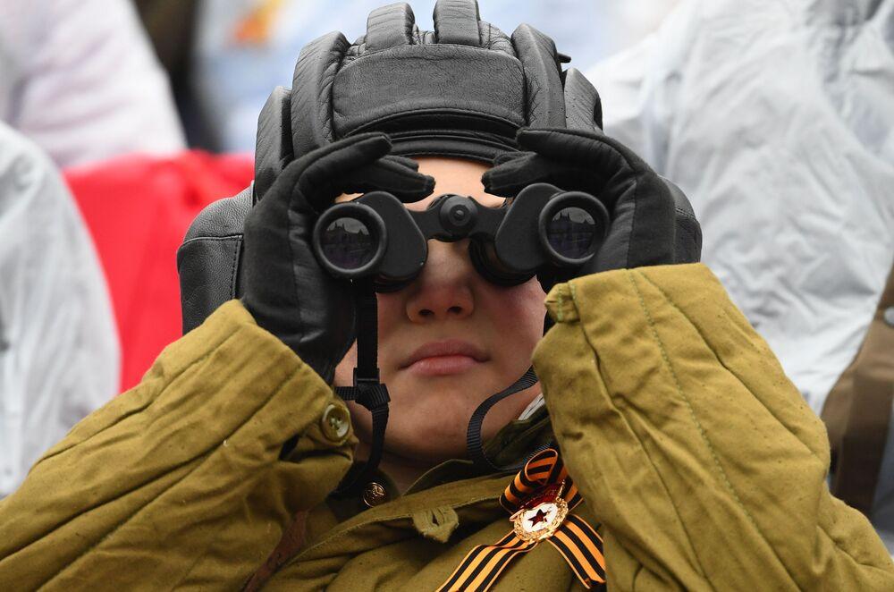 Menino olha através de binóculos durante a Parada da Vitória em Moscou, Rússia, 9 de maio de 2021