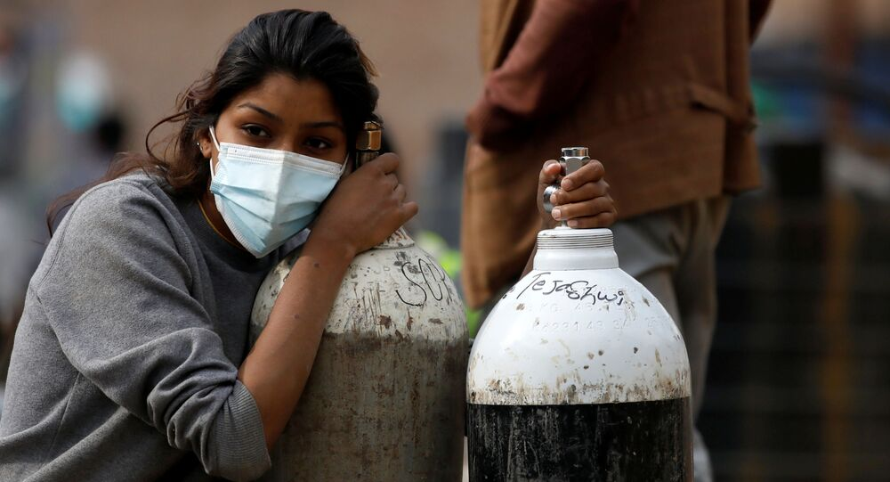 Em Kathmandu, na Índia, uma mulher segura cilindros de oxigênio após abastecê-los em uma fábrica, em 9 de novembro de 2021