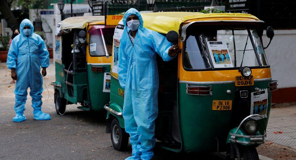 Em Nova Deli, na Índia, profissionais aguardam ao lado de ambulâncias para transportar pacientes de COVID-19, em 5 de maio de 2021