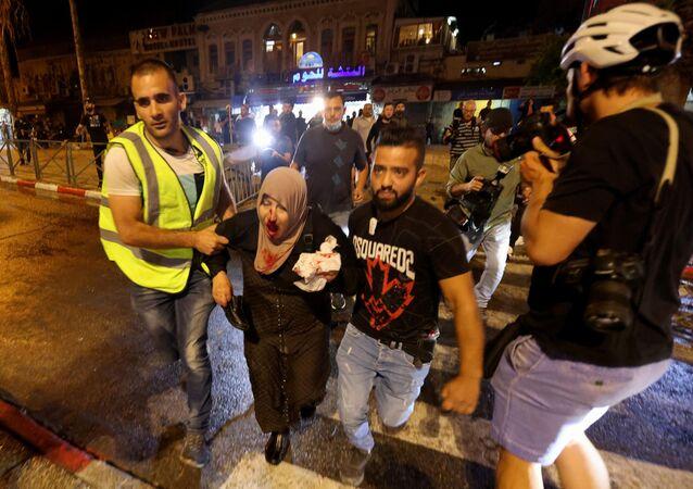 Em Jerusalém, uma mulher palestina ferida é levada embora durante confrontos com a polícia de Israel em meio ao mês sagrado do Ramadã, em 8 de maio de 2021