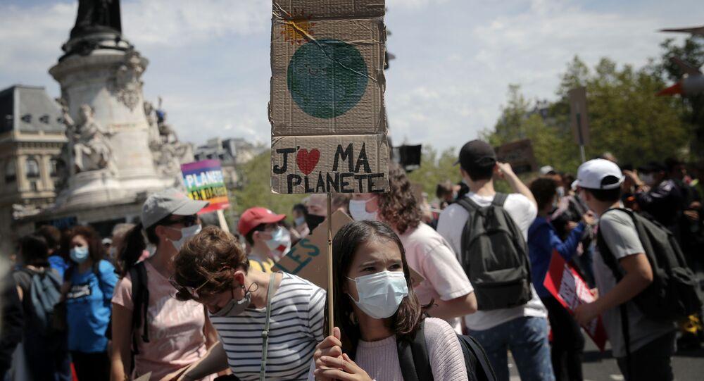 Uma manifestante segura um cartaz durante uma manifestação contra as mudanças climáticas em Paris, em 9 de maio de 2021. Milhares de pessoas foram às ruas de Paris e outras cidades para pedir medidas de combate às alterações climáticas