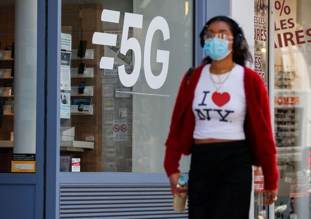 Mulher usando máscara facial protetora passa por placa de rede de dados 5G em uma loja de telefonia móvel em Paris, França, 22 de abril de 2021