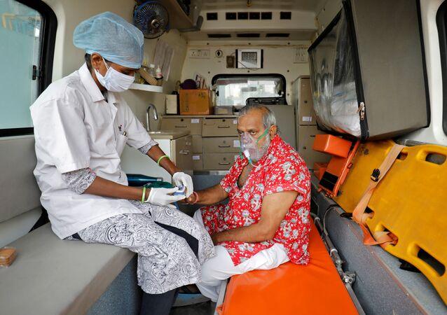 Paramédico usa oxímetro para medir o nível de oxigênio de paciente dentro da ambulância enquanto espera ser internado no hospital em Ahmedabad, Índia, 22 de abril de 2021