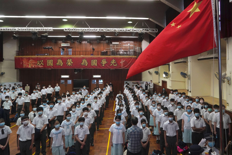 Alunos participam de uma cerimônia de hasteamento da bandeira durante o Dia da Educação para a Segurança Nacional em uma escola secundária, em Hong Kong, em 15 de abril de 2021