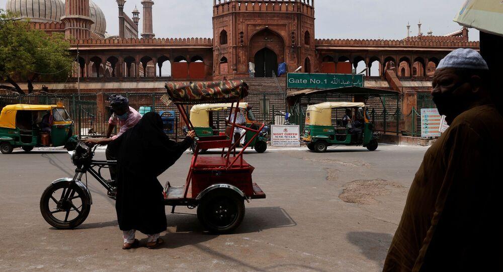 Uma mulher senta-se em um riquixá em frente ao Jama Masjid ou Grande Mesquita em Jumat-ul-Vida em um dos bairros antigos de Delhi, Índia, 7 de maio de 2021;