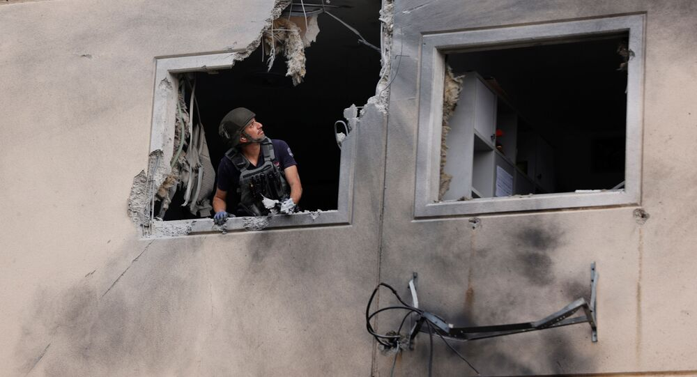 Especialista do esquadrão antibombas da polícia de Israel observa pela janela de um prédio residencial danificado após ser atingido por um foguete lançado da Faixa de Gaza, no dia 11 de maio de 2021