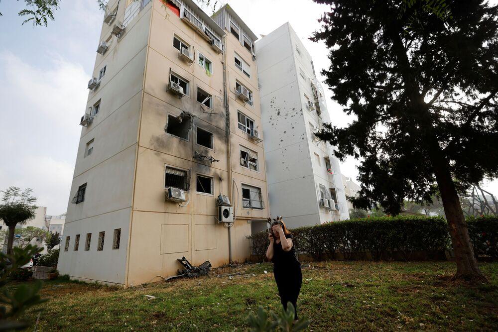 Mulher caminha perto de um prédio residencial danificado por um foguete lançado da Faixa de Gaza