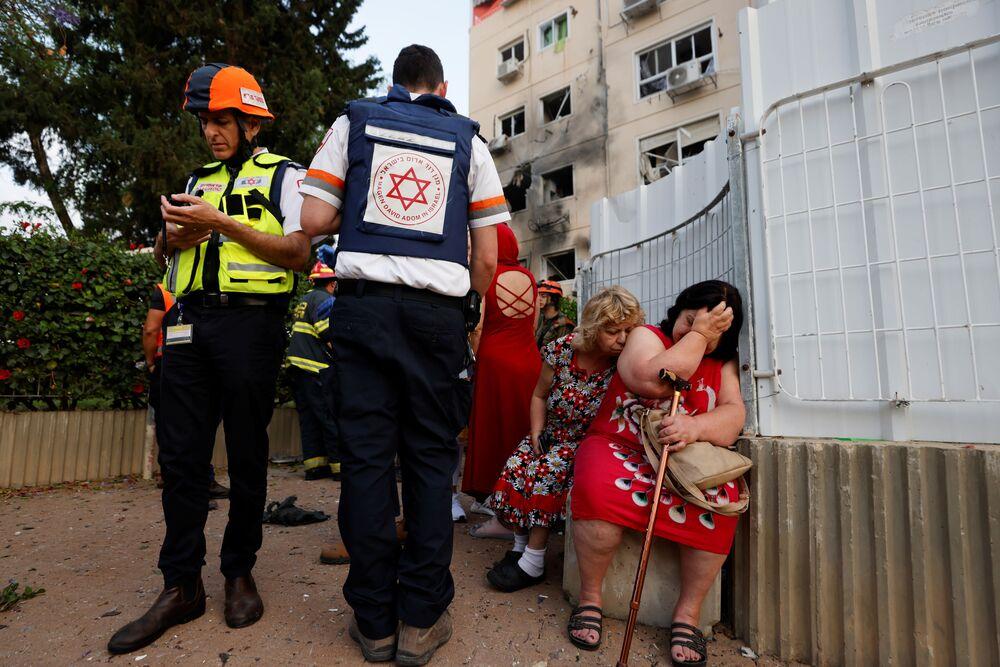 Médicos israelenses atendem mulheres perto de uma construção danificada por um foguete lançado da Faixa de Gaza