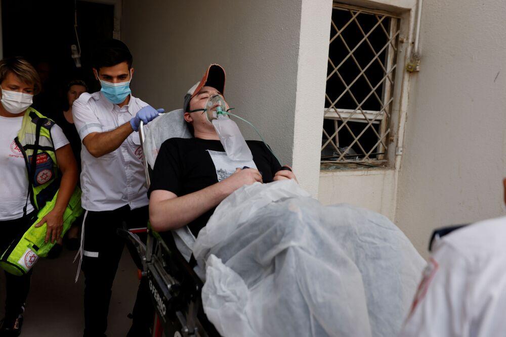 Médicos israelenses evacuam um homem ferido após foguete lançado de Gaza atingir prédio residencial no sul de Israel