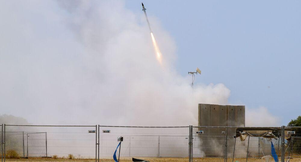 Soldado israelense se protege enquanto míssil do sistema antiaéreo Cúpula de Ferro é disparado para interceptar foguete lançado de Gaza