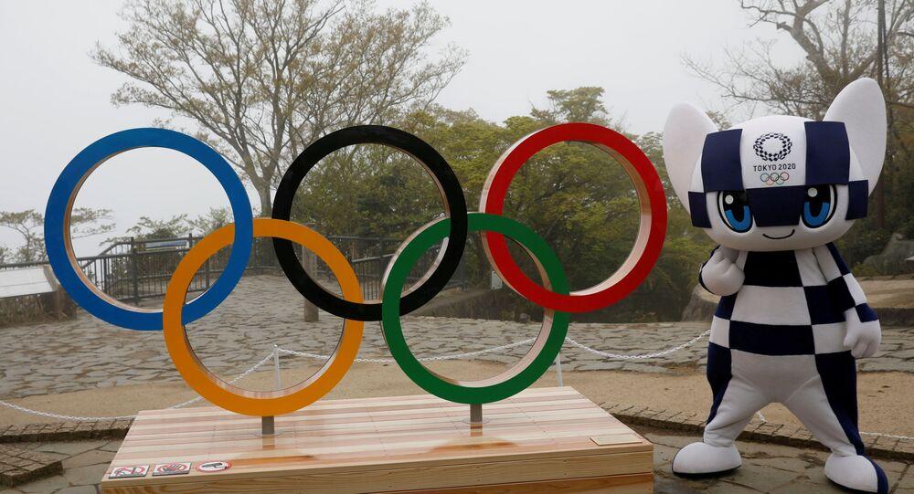 O mascote dos Jogos Olímpicos de Tóquio 2020, Miraitowa, posa ao lado símbolo olímpico, em Tóquio, no Japão, no dia 14 de abril de 2021
