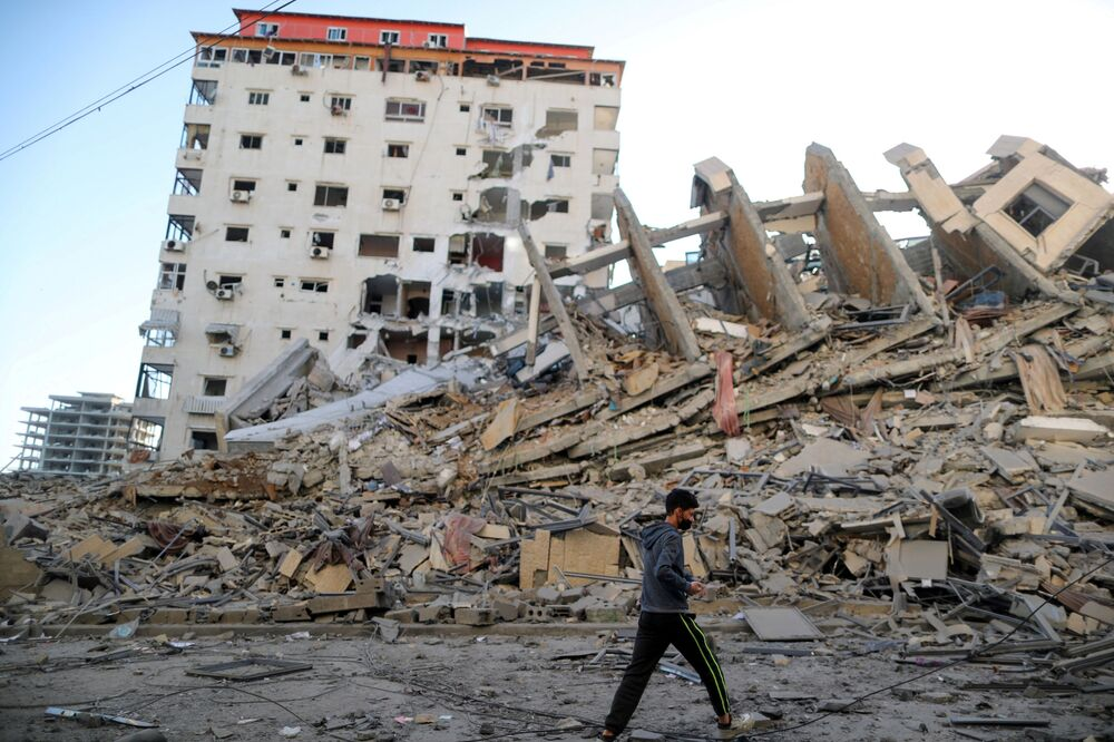 Garoto palestino caminha ao lado das ruínas de um prédio, que foi destruído pelos ataques aéreos israelenses em Gaza
