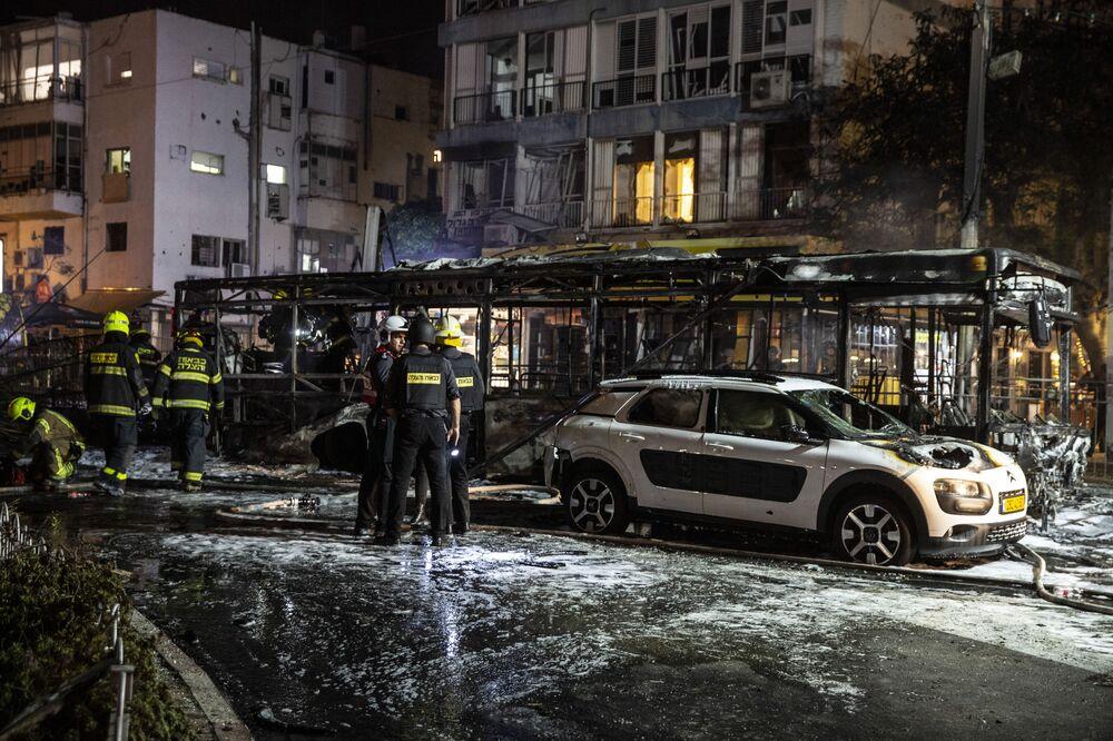 Bombeiros israelenses trabalham onde um foguete, lançado de Gaza, atingiu a cidade de Holon, próximo de Tel Aviv
