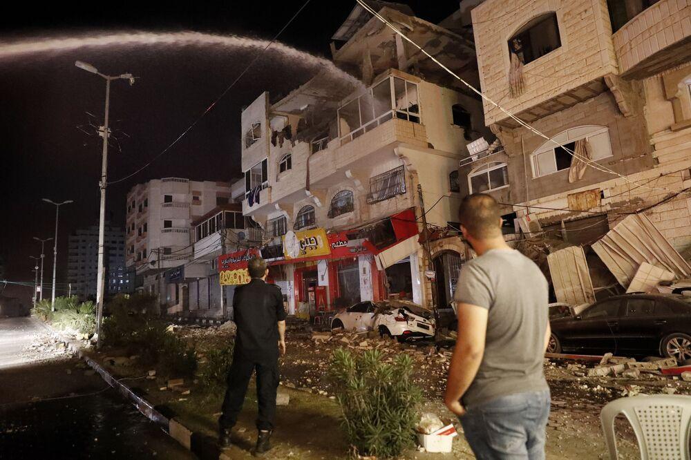 Bombeiros combatem incêndio em prédio após ser atingido pelos ataques aéreos israelenses, na cidade de Gaza