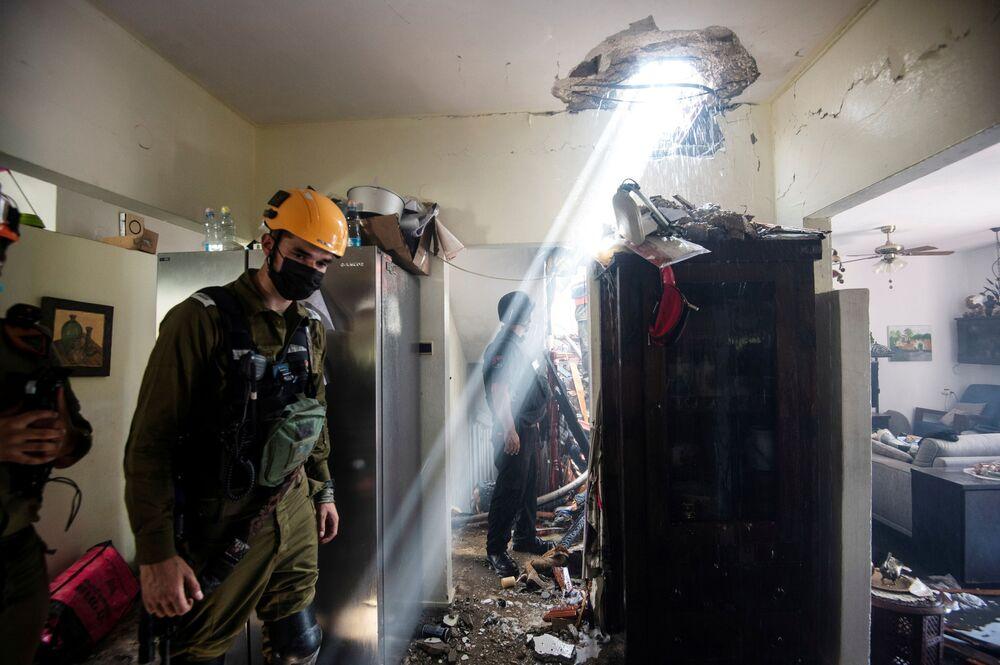 Soldados trabalham em um prédio danificado por um foguete lançado de Gaza, contra Ashdod, no sul de Israel
