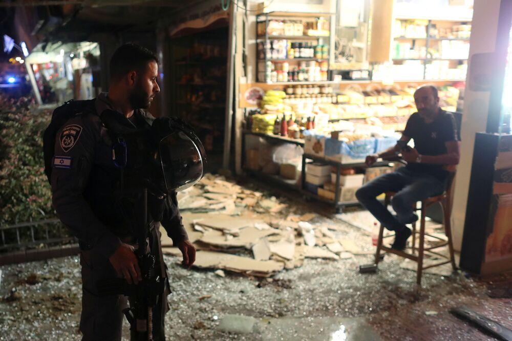 Agente das forças de segurança de Israel fala com um homem no local atingido por um foguete lançado de Gaza, em Holon, Israel