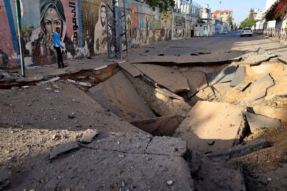 Palestino em frente a uma cratera gigante em Gaza