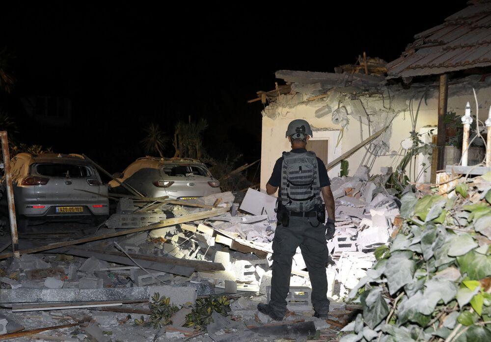 Oficial israelense inspeciona os danos em uma casa atingida por foguetes na cidade de Yehud, próximo de Tel Aviv, em Israel