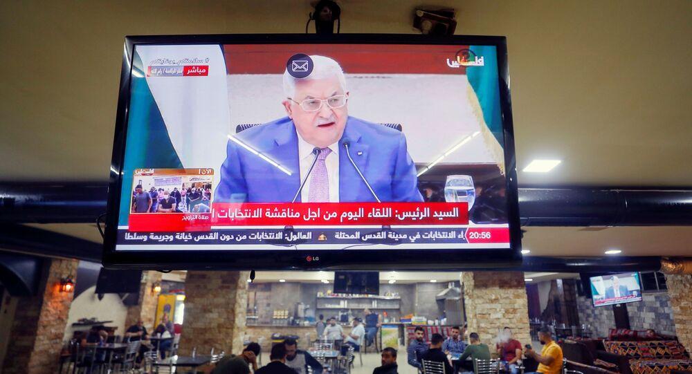 Uma tela exibindo uma transmissão ao vivo do discurso do presidente palestino Mahmoud Abbas durante reunião para discutir as próximas eleições em Ramallah, na Cisjordânia, em 29 de abril de 2021.