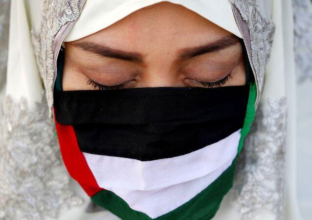 Manifestante participa de ato em solidariedade à Palestina em Jacarta, Indonésia, 13 de maio de 2021