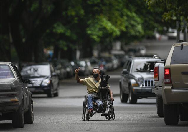 Homem usa máscara protetora enquanto pede dinheiro em farol em Caracas, Venezuela, 9 de maio de 2021