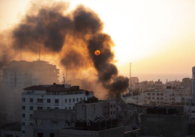 Fumaça é vista saindo de um prédio destruído após ter sido bombardeado por Israel na cidade de Gaza, 12 de maio de 2021