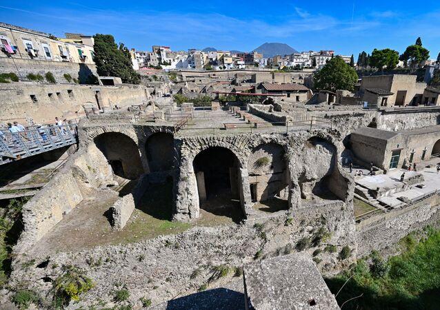 Uma vista geral mostra o sítio arqueológico de Herculano em Ercolano, perto de Nápoles, com o vulcão do Monte Vesúvio ao fundo