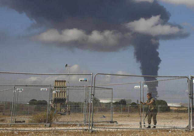 Um soldado israelense fica de guarda próximo a um sistema de defesa aérea Cúpula de Ferro enquanto a fumaça sobe de um tanque de petróleo em chamas após ser atingido por um foguete na Faixa de Gaza, quarta-feira, 12 de maio de 2021