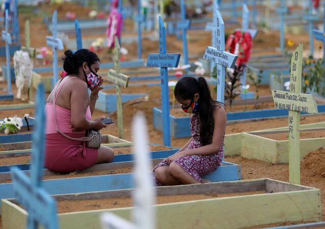 Mulher e criança sentam perto de cova onde foi enterrada vítima do coronavírus no cemitério Parque Taruma, em Manaus