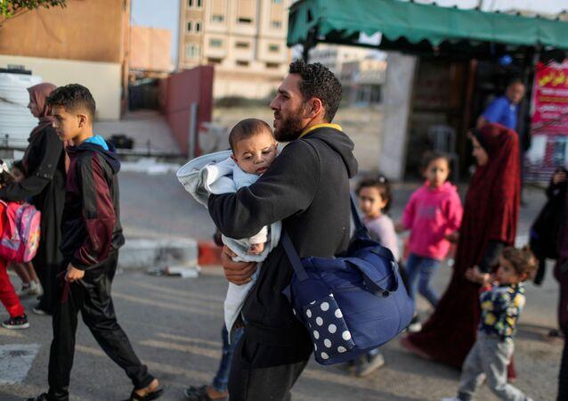 Palestinos fogem de suas casas durante ataques aéreos israelenses, no norte da Faixa de Gaza, em 14 de maio de 2021