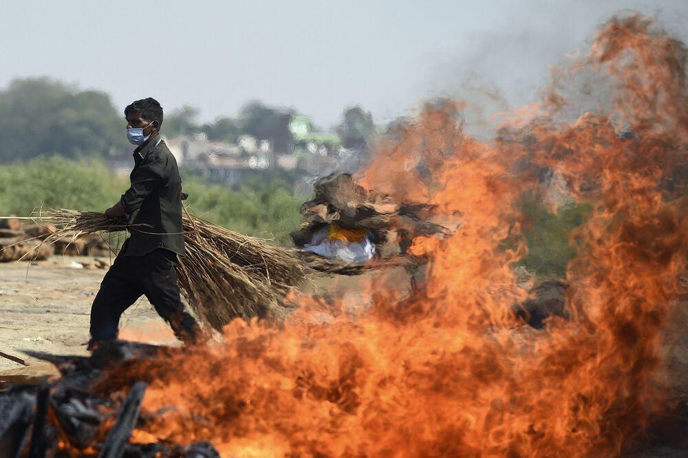 Funcionário passa ao lado de pira funerária de uma pessoa morta com COVID-19, na Índia, 8 de maio de 2021