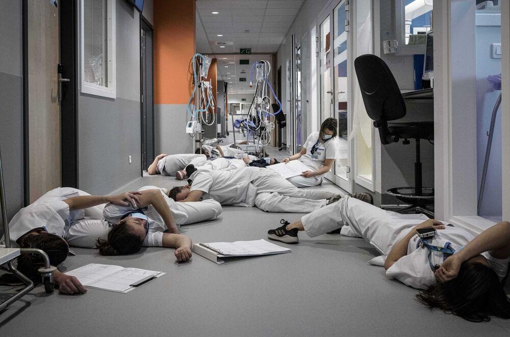 Enfermeiras e funcionários de saúde belgas deitados no chão na unidade de terapia intensiva do hospital em Liège, para assinalar o Dia Internacional dos Enfermeiros, em 12 de maio