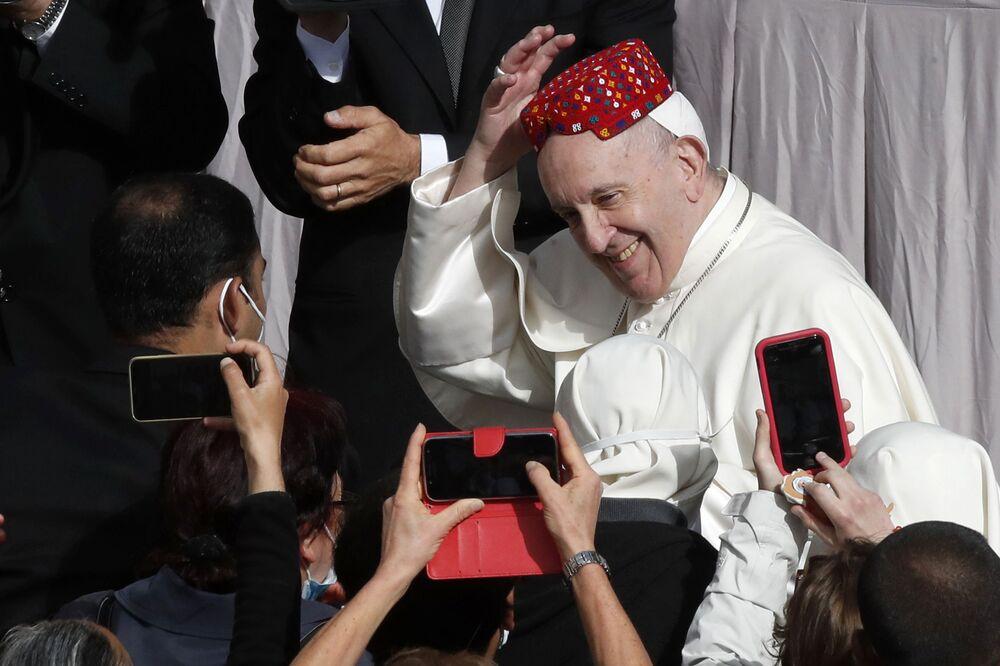 Papa Francisco sorrindo após uma das pessoas ter lhe colocado um chapéu durante a audiência semanal do Papa no Vaticano, 12 de maio de 2021