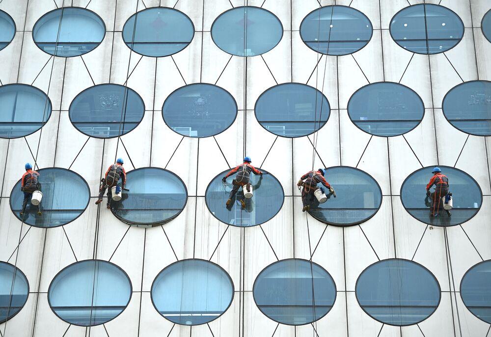 Empregados lavam janelas em prédio de Pequim, China, 12 de maio de 2021