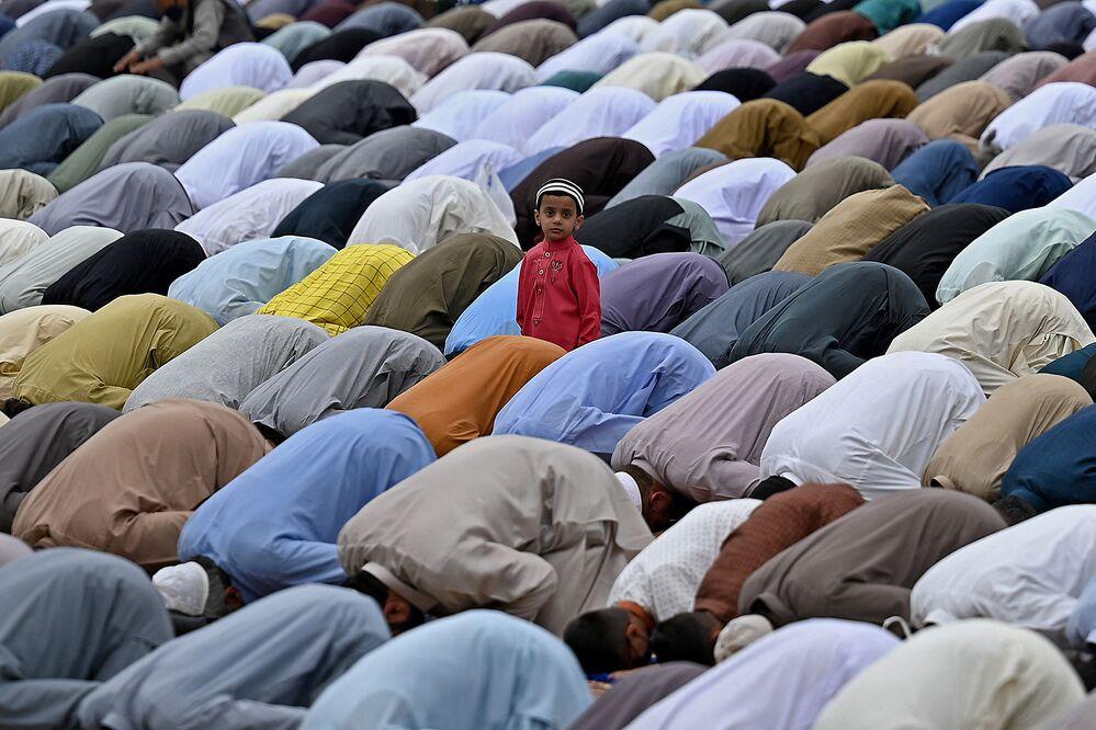 Criança olha para muçulmanos que rezam por ocasião do Eid al-Fitr, que marca o final do mês sagrado do Ramadã, na cidade paquistanesa de Rawalpindi, 13 de maio de 2021