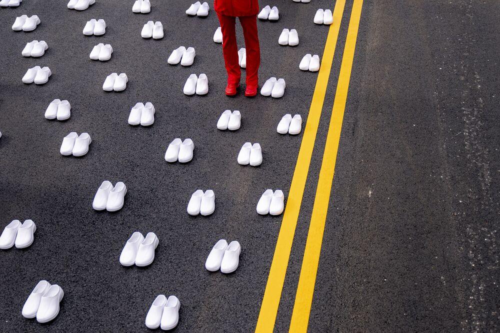 Mulher em uniforme de enfermeira, rodeada por centenas de pares de sapatos brancos representando as 402 enfermeiras que morreram da COVID-19, perto da Casa Branca em Washington, 12 de maio de 2021