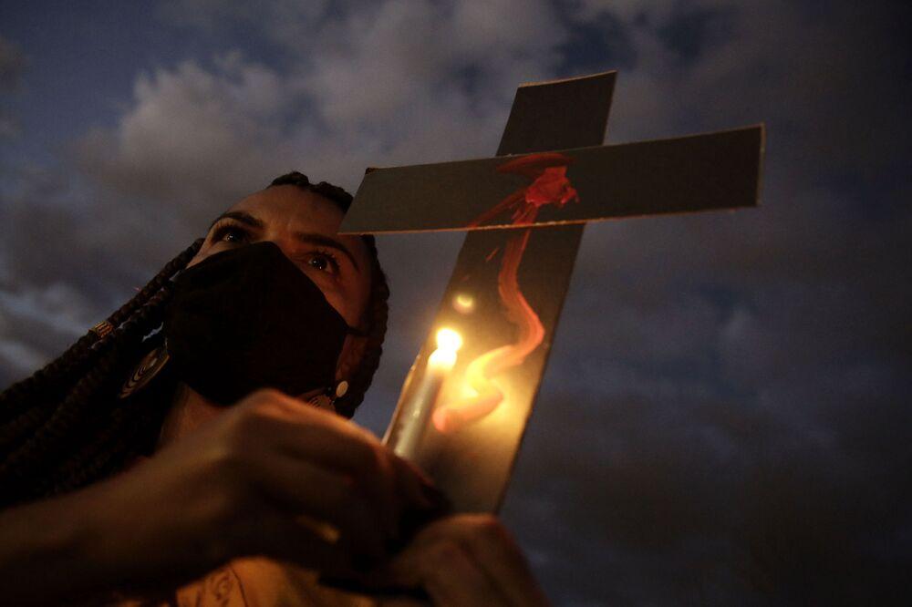 Ativista carregando uma cruz em homenagem às vítimas entre a população negra no dia da Abolição da Escravatura, 13 de maio de 2021