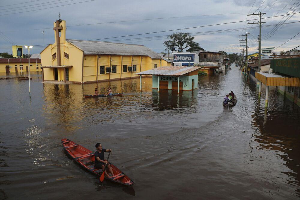 Residentes do Amapá navegando em ruas inundadas, 13 de maio de 2021