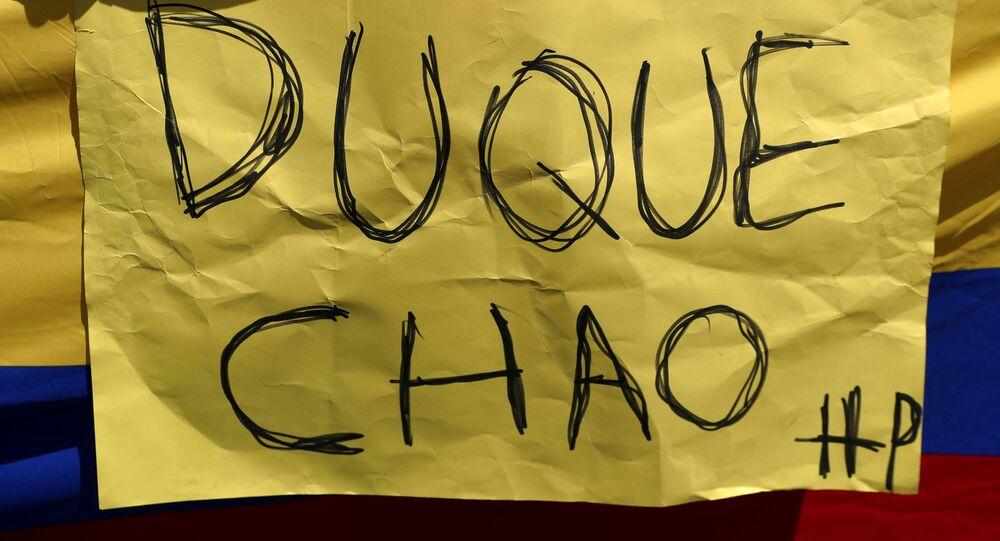 Mulher segura bandeira colombiana e cartaz em Madri, durante marcha de apoio às manifestações na Colômbia contra a reforma fiscal do governo do presidente Iván Duque e contra a violência policial, Espanha, 8 de maio de 2021