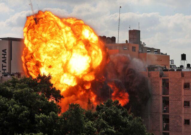 Uma foto tirada em 13 de maio de 2021 mostra uma bola de fogo no prédio que foi destruído em um ataque aéreo israelense na cidade de Gaza