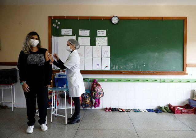 Em Campo Bom, no estado brasileiro do Rio Grande do Sul, uma professora é vacinada contra a COVID-19 com o imunizante da AstraZeneca/Oxford, em 12 de maio de 2021