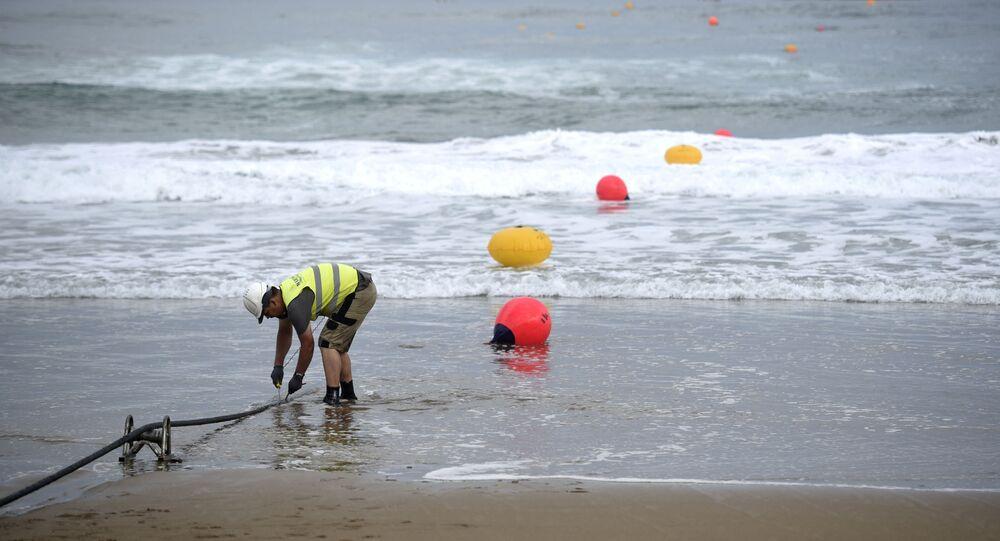 Operário trabalha na ancoragem de um cabo submarino de fibra óptica