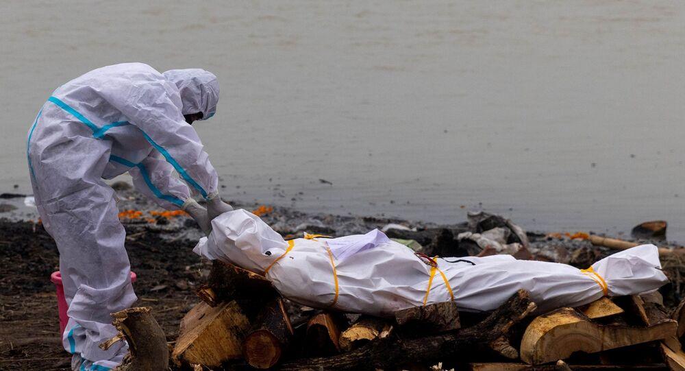 Homem usando traje de proteção toca no corpo de seu parente que morreu de COVID-19 antes de sua cremação nas margens do rio Ganges em Garhmukteshwar, no estado de Uttar Pradesh, Índia, 6 de maio de 2021