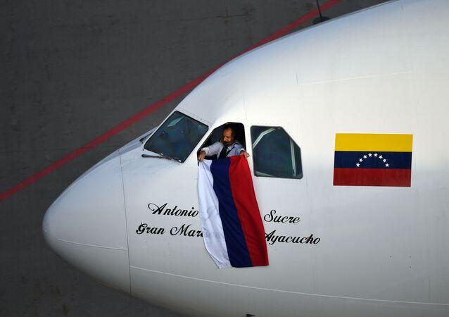 Em Moscou, um piloto da companhia aérea venezuelana Conviasa mostra uma bandeira da Rússia após a chegada ao aeroporto de Vnukovo no primeiro voo da rota direta entre a capital russa e Caracas, em 15 de maio de 2021